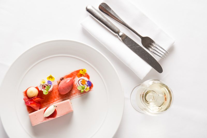 strawberry dessert with glass of white wine