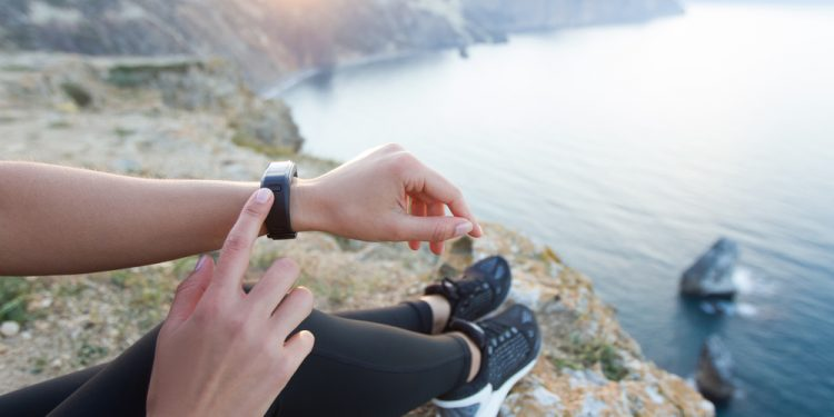 girl on cliff edge by water pointing to fitness tracker on wriist