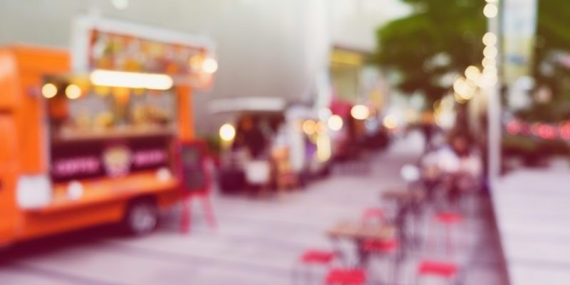 blurry pictureof a food truck with stools
