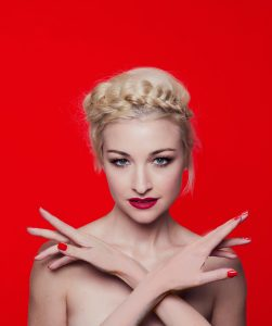 Australian artist Kate Miller-Heidke posing with hands in front of her