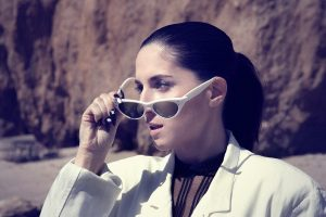 Nite Jewel, also known as Ramona Gonzalez, takes off white rimmed sunglasses for a pose shot