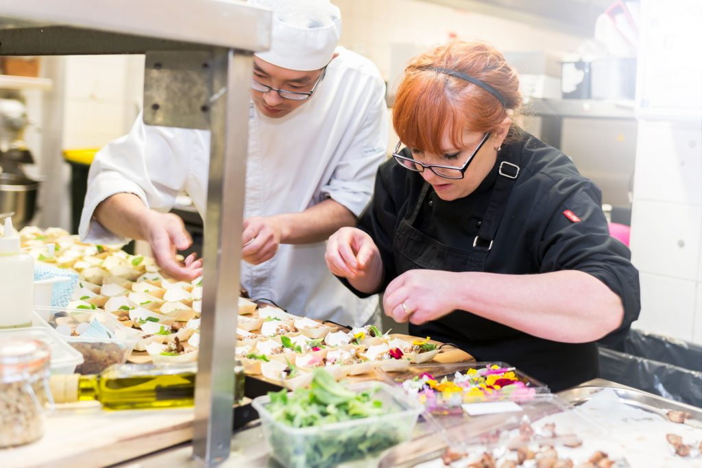 Executive Chef Jennie Tressler plating up canapés in a commercial kitchen