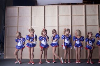 A line of blonde girls wearing matching costumes