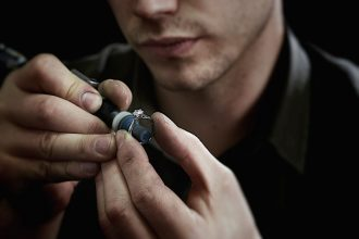 close-up of a jeweller preparing a diamond and silver engagement ring