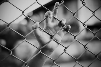 A girl's hand rests on a fence. Image: Chatiyanon