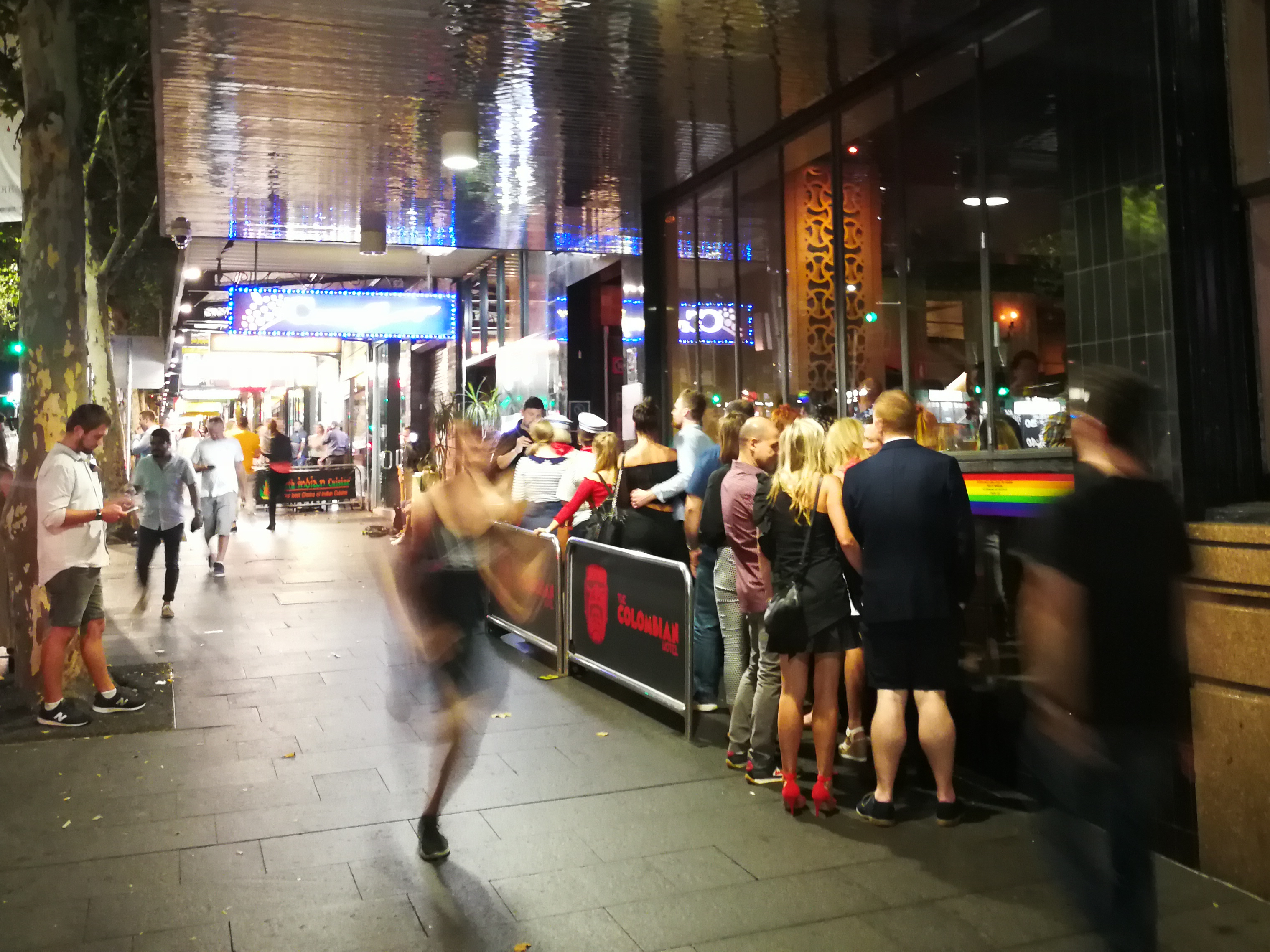 A runner dashes down Oxford Street while revellers wait in line. Image: Christopher Kelly