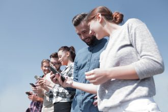 Various people checking out their smartphones. Image: ASDF_MEDIA [Shutterstock]