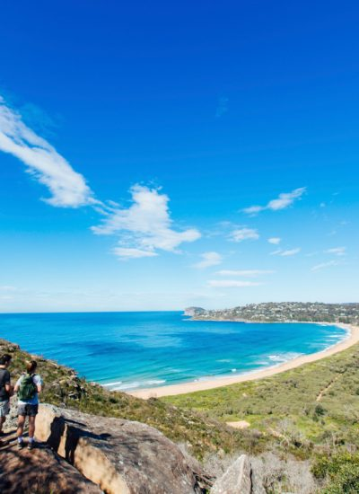 Couple enjoying a scenic coastal hike on the Barrenjoey Lighthouse Walk in Palm Beach, Sydney. Image: Destination NSW