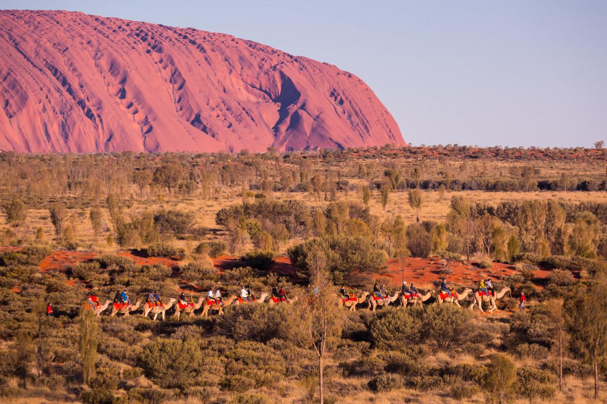 Camel riders near Uluru. Image: Shutterstock