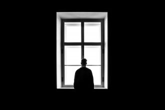 Man at window. Photographed by Sasha Freemind. Image via Unsplash