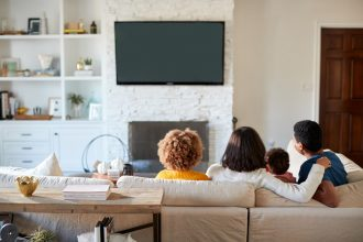 Family watching TV in nice living room seen from behind