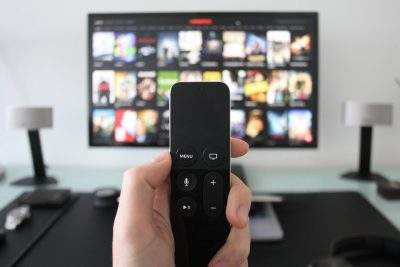tv remote in foreground with screen with movie options out of focus in background