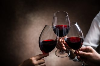 3 red wine glasses toasting. Photographed by taa22. Image via Shutterstock