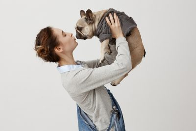 Girl holding dog. Photographed by Cookie Studio. Image via Shutterstock
