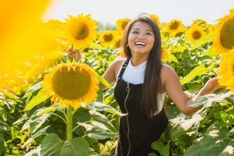 Happy woman amongst sunflowers. Photographed by Courtney Cook. Sourced via Unsplash