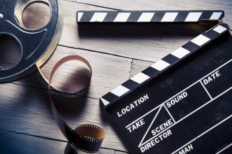 Movie clapper and film reel. Photographed by Fer Gregory. Image via Shutterstock