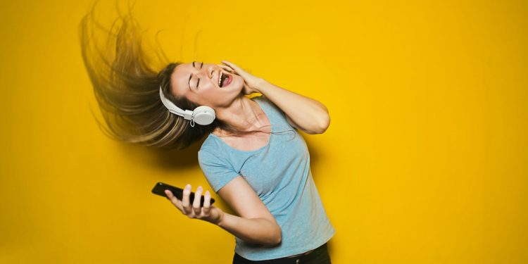 Woman singing and listening to music. Photographed by Bruce Mars. Image via Unsplash