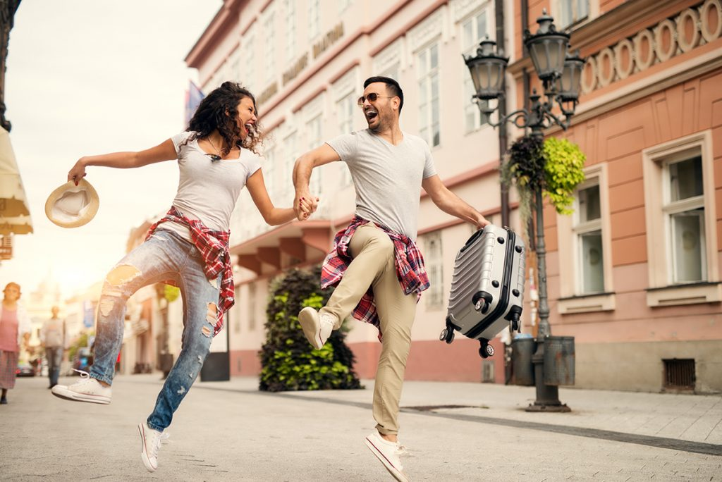 Happy couple running down the street whilst on holiday. Image via shutterstock