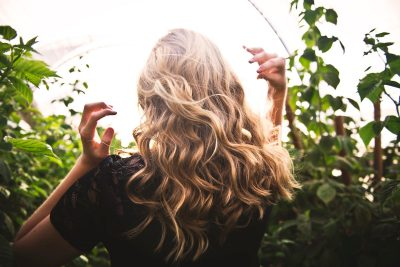 Blonde haired woman in garden. Hair. Photographed by Tim Mossholder. Image via Unsplash