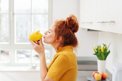Woman holding yellow piggy bank. Image purchased via shutterstock.