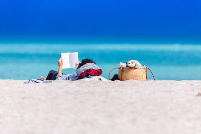 Man reading a book on the beach. Photographed by Dan Dumitriu. Sourced via Unsplash