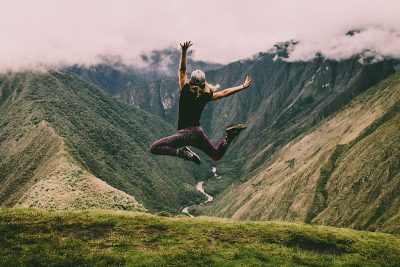 Woman jumping in the air. Photo by Peter Conlan. Image via Unsplash