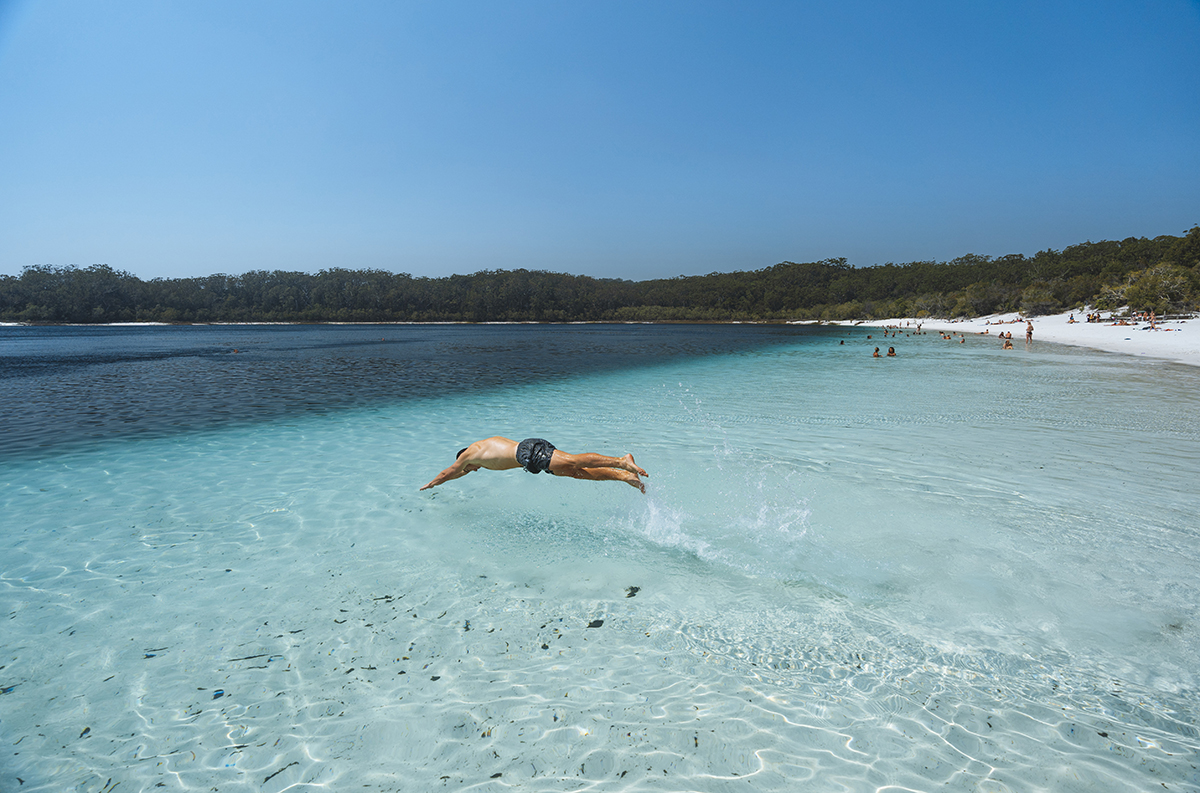 Diving Into Lake McKenzie. Supplied by Tourism and Events Queensland. Photographed by Reuben Nutt.