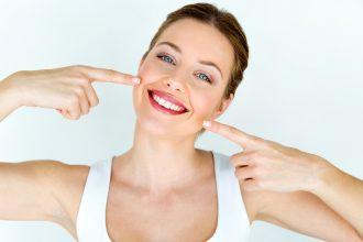 Woman smiling with teeth. Photographed by Josep Suria. Image via Shutterstock