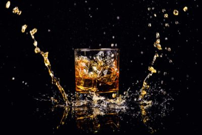 Isolated shot of whiskey with splash on black background. Photographed by The Len. Image sourced via Shutterstock.