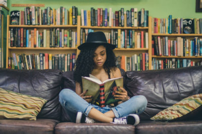 Woman reading book, short story. Photographed by Seven Shooter. Image via Unsplash
